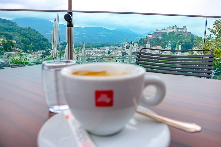 coffee cup and plate on table overlooking castle views of old town salzburg m32 restaurant