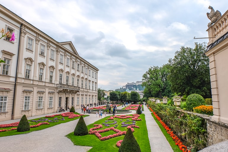 green garden paths with large palace beside mirabell gardens salzburg